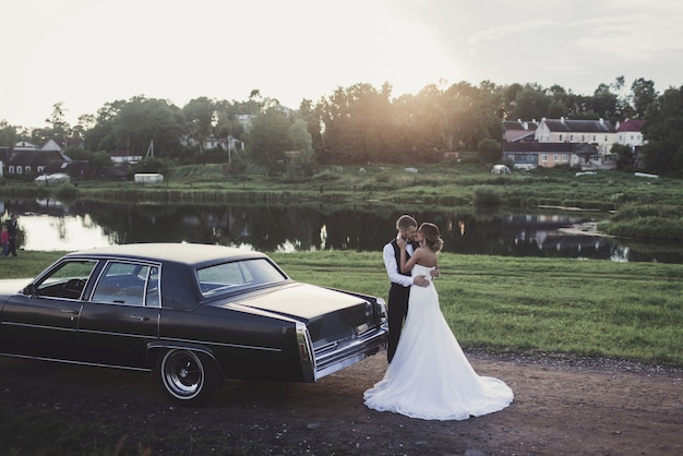 Sonnenscheinporträt der glücklichen braut und des bräutigams