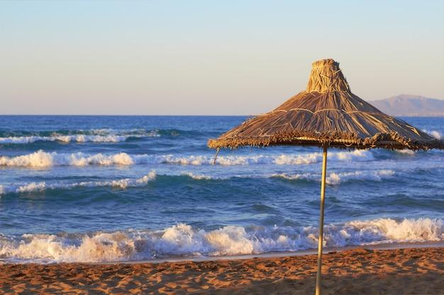 Sonnenschirm auf dem seestrand bei sonnenuntergang mit wellen auf hintergrund. platz für text