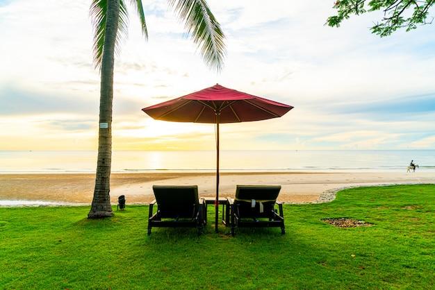 Sonnenschirm mit stuhl mit meeresstrand und sonnenaufgang am morgen