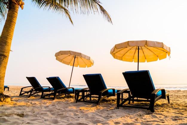 Sonnenschirm strand mit palme und meeresstrand bei sonnenaufgang
