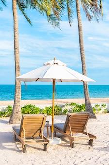 Sonnenschirm und liegestuhl um außenpool im hotelresort mit meeresmeerstrand und kokospalme