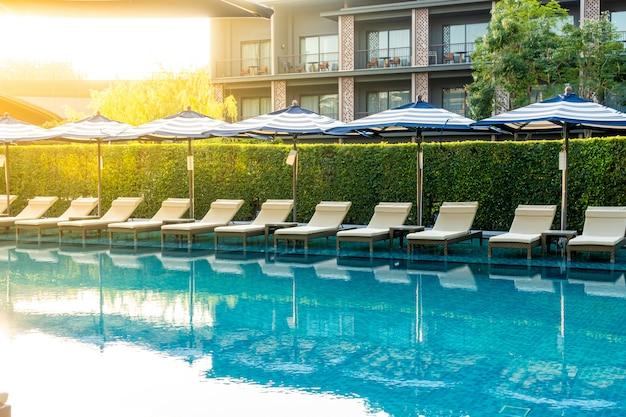 Sonnenschirm und poolbett rund um den außenpool im hotelresort für urlaubsreisen