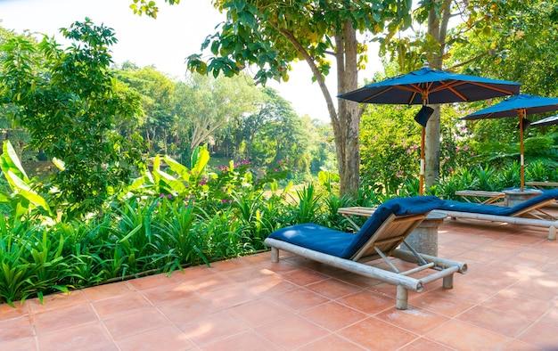 Sonnenschirm und poolbett rund um den pool mit blick auf den fluss