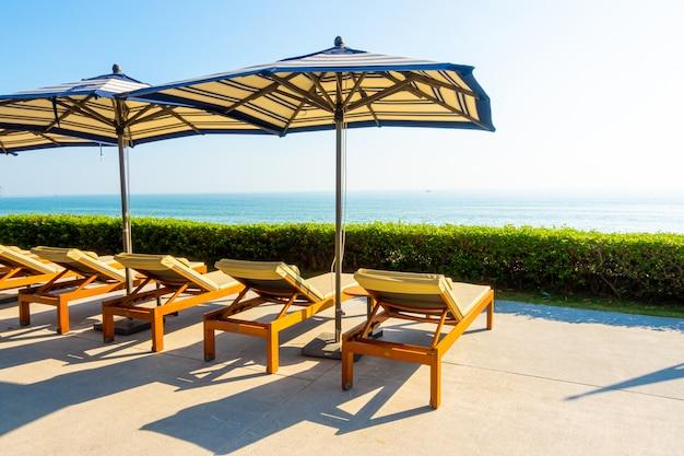 Sonnenschirm und stuhl rund um den außenpool im hotel und resort
