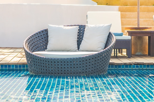 Sonnenschirm und stuhl um außenpool im hotelresort mit meerblick für reiseurlaub