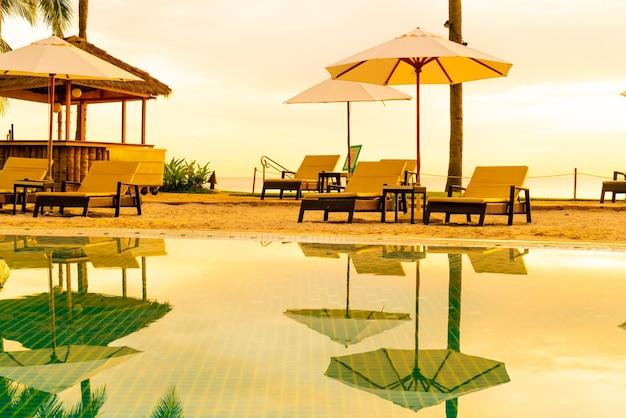 Sonnenschirm und stuhl um den pool im hotelresort mit sonnenaufgang am morgen - urlaubs- und urlaubskonzept
