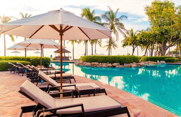 Sonnenschirm und stuhl um den pool im resorthotel für urlaubsreisen und urlaub in der nähe des meeres