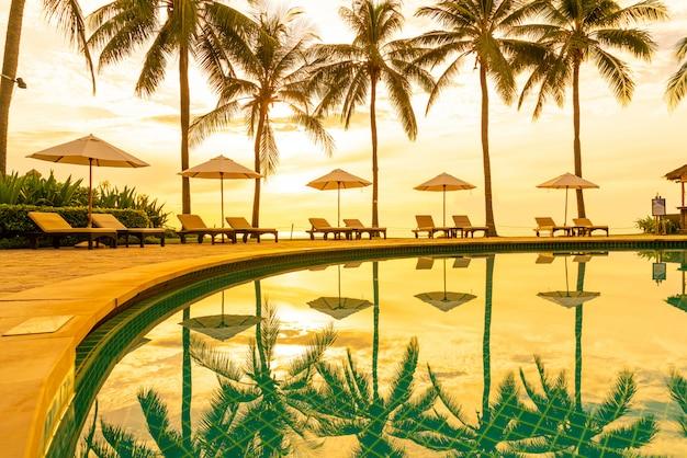 Sonnenschirm und stuhl um den pool im resorthotel für urlaubsreisen und urlaub in der nähe des meeresstrandes bei sonnenuntergang oder sonnenaufgang
