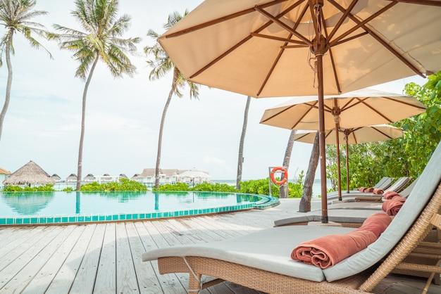 Sonnenschirm und stuhl um den pool im resorthotel