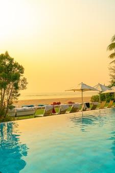 Sonnenschirm und stuhl um pool mit meerblick