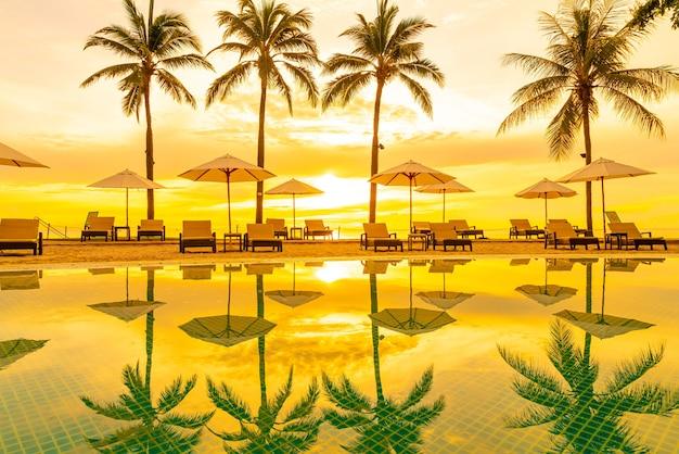 Sonnenschirm und stuhl um schwimmbad im hotelresort mit sonnenaufgang am morgen - urlaub und ferienkonzept