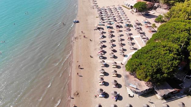 Sonnenschirme auf sand gewaschen von ruhigem klarem wasser des türkisfarbenen meeres im mittelmeer.
