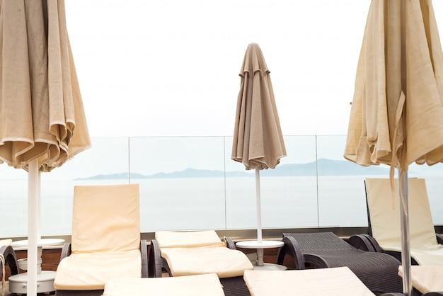 Sonnenschirme farbe beige und liegen in der nähe von schwimmbad mit meerblick.