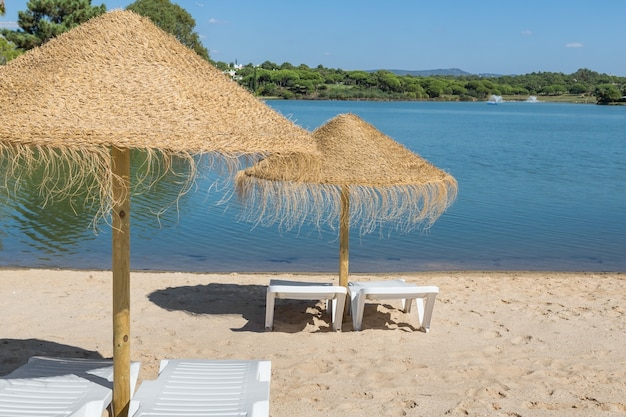 Sonnenschirme und sonnenliegen am strand in der nähe des sees. sommerurlaub.