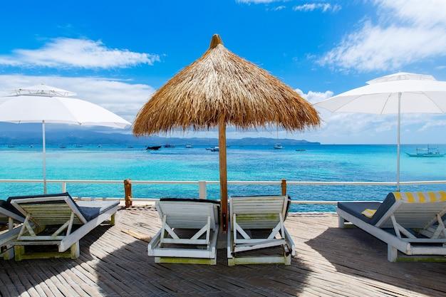 Sonnenschirme und strandliegen mit blick auf das tropische meer. sommerferienkonzept.