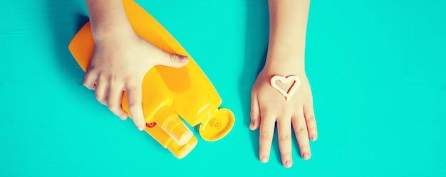 Sonnenschutz an der hand eines kindes.