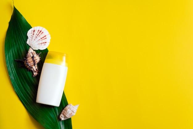 Sonnenschutz auf einem palmblatt auf gelbem grund und neben muscheln. creme zum sonnenschutz. uv-schutz