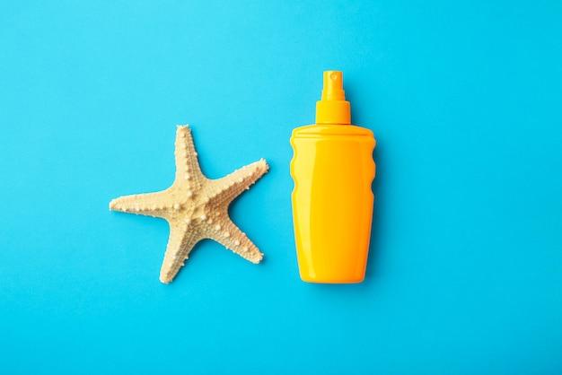 Sonnenschutzflasche mit seestern auf blauem hintergrund.