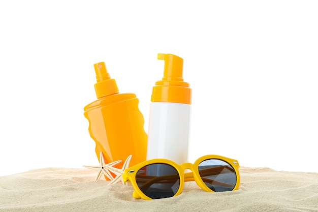 Sonnenschutzmittel mit seestern und sonnenbrille auf klarem meersand lokalisiert auf weißem hintergrund. sommerurlaub