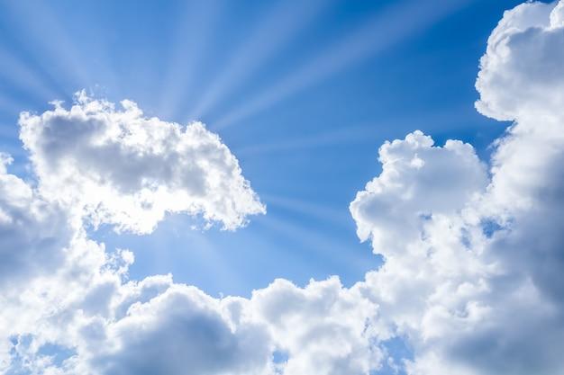 Sonnenstrahlen, die durch die wolken auf blauem himmel brechen.