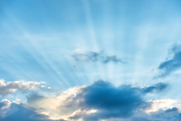Sonnenstrahlen, die durch wolken am blauen sonnenunterganghimmel scheinen