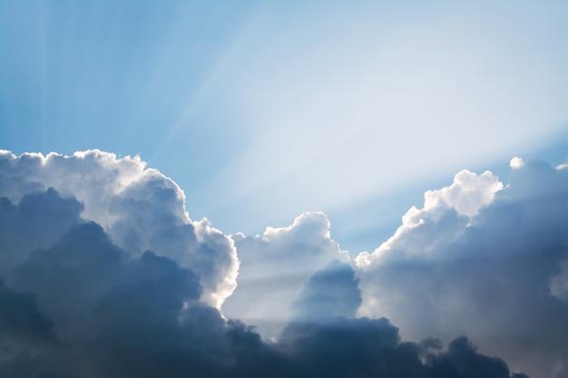 Sonnenstrahlen hinter den dramatischen gewitterwolken vor dem regen am abend