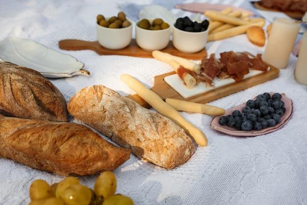 Sonnenstrahlen o sommer-picknickdecke mit leckerem essen und snacks drauf. sommerwochenenden