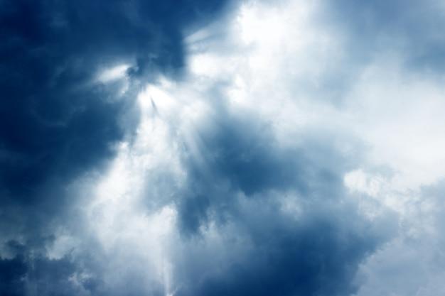 Sonnenstrahlen scheinen mit hellem gott und dunklen wolken herab.
