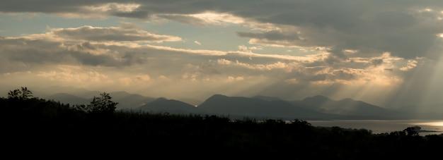 Sonnenstrahlen während des sonnenaufgangs über dem berg
