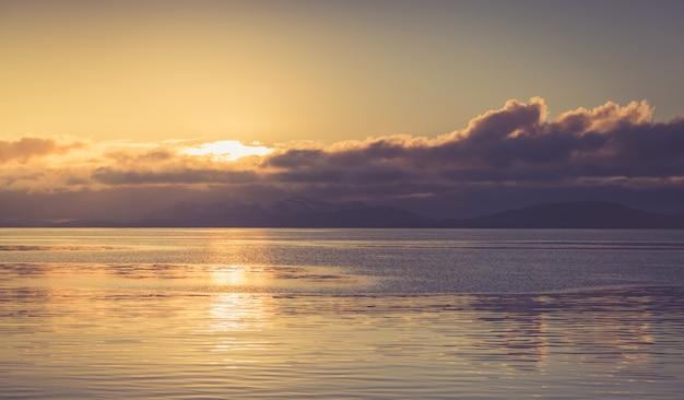 Sonnenuntergang am bewölkten himmel mit gelassenheit meer und silhouetten der berge.