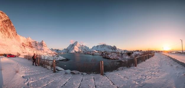 Sonnenuntergang am fischerdorf mit schneebedeckten berg bei reine