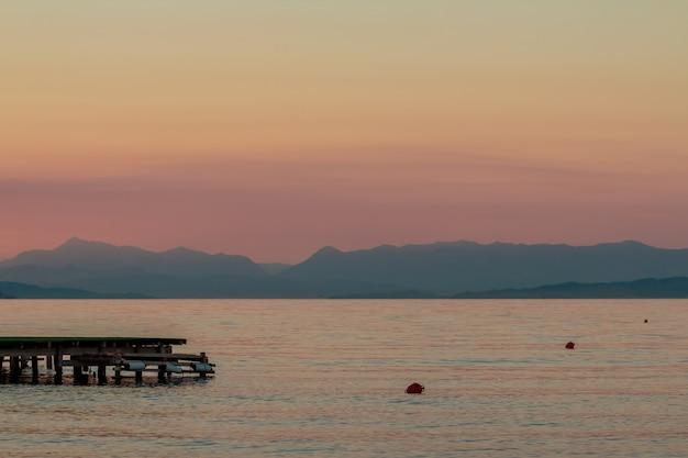 Sonnenuntergang am fluss. orange sonnenunterganglandschaft mit pier und männern. klare orange himmelansicht. romantischer abendsonnenuntergang in den tropen. rustikales hölzernes pier- und bootsschattenbild. sonnenuntergangsbeobachter. sonne über berg