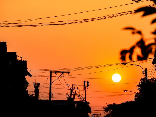 Sonnenuntergang am himmel hinter elektrischem pfosten und gebäude des schattenbildes.