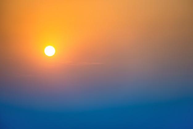 Sonnenuntergang am himmel mit großer sonne, blauen, orangen und roten dramatischen farben