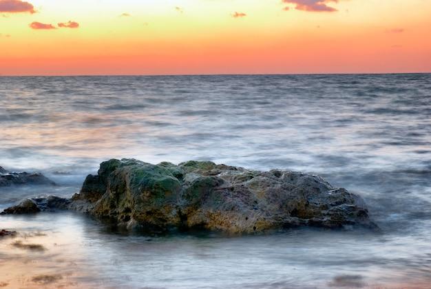 Sonnenuntergang am meer. landschaft mit großem felsen und schönem orangefarbenem himmel.