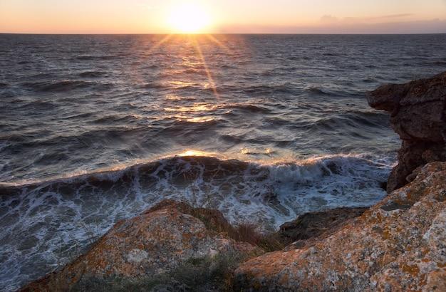 Sonnenuntergang am meer mit brandung und felsiger küste