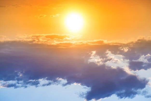 Sonnenuntergang am orangefarbenen himmel mit großer sonne und blauer wolke