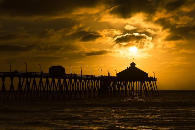 Sonnenuntergang am pier mit schönem bewölktem himmel
