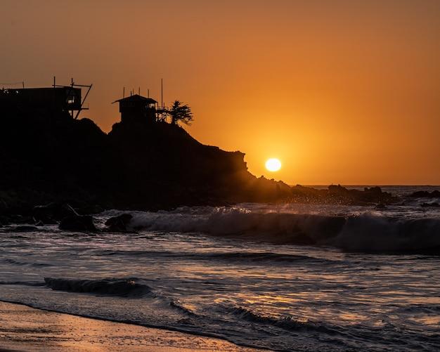 Sonnenuntergang am quintay strand, chile, mit einem kleinen haus slihouette