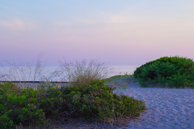 Sonnenuntergang am strand mit fließenden bunten sonnenstrahlen durch die wolken