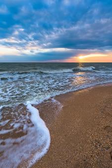 Sonnenuntergang am strand mit langer küste, sonne und dramatischen himmel