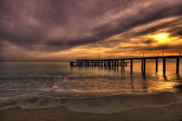 Sonnenuntergang am strand neben dem pier