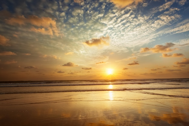 Sonnenuntergang am strand von baga. goa