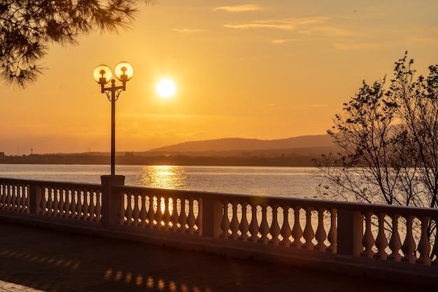 Sonnenuntergang am ufer des resorts mit balustrade und laternen. die sonne geht in den bergen unter