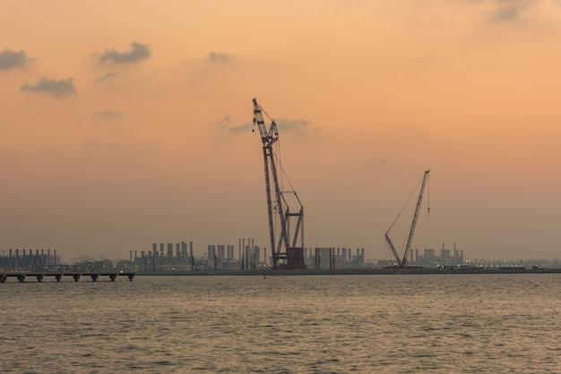 Sonnenuntergang an der dubai-seehafen-uae-schattenbildkraniche auf einem hellen himmelhintergrund