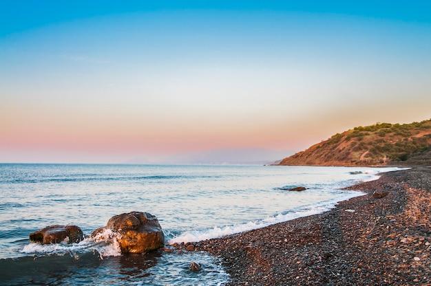Sonnenuntergang an der küste, am felsigen strand und am blauen himmel.