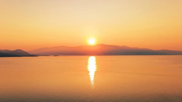Sonnenuntergang an der küste des ionischen meeres, griechenland. strahlende sonne, land in der ferne, spiegelungen im wasser