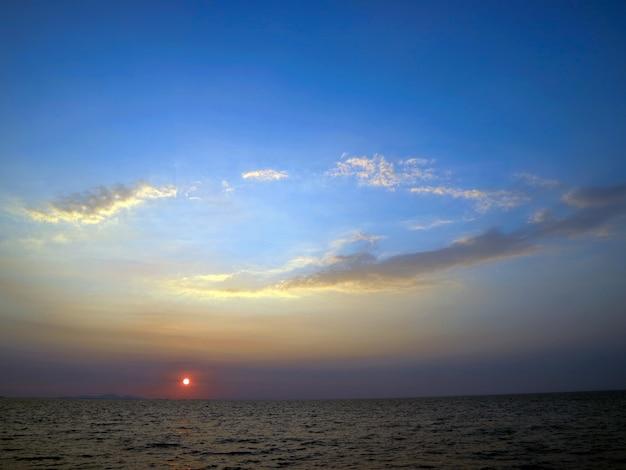 Sonnenuntergang auf dem blauen himmel des meeres und der ovalen wolke