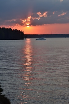 Sonnenuntergang auf dem pestovo-reservoir, sonnenuntergang auf dem see, weiße yacht bei sonnenuntergang