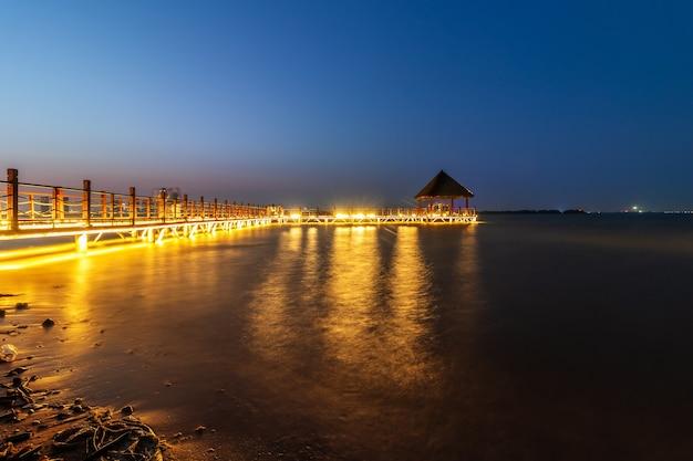 Sonnenuntergang auf der insel malediven, luxuriöses wasservillenresort und hölzerner pier. schöner himmel und wolken und strandhintergrund für sommerferienurlaub und reisekonzept